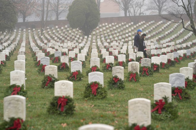 In this Dec. 14, 2019, file photo, people walk among headstones with holiday wreaths in Arlington National Cemetery during Wreaths Across America Day in Arlington, Virginia.
