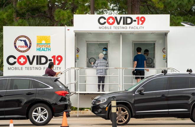People register to be tested Friday at a COVID-19 testing center in the Town Center at Boca Raton mall parking lot.