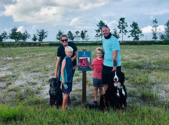 Sasha Hulscher, left, and Ashton Hulscher stand with their sons, Aiden and Ethan, and their two dogs in the lot of their future Arden home built by Kenco. The Hulschers are among the many people who decided to build a new home during the coronavirus pandemic.