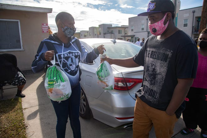 Tanissia Bufkin, left, hands a frozen turkey to Keon Stapleton at the Sierra Vista turkey giveaway during an event organized by Georgia Brownlee, president of the Sierra Vista Residents Council. Without Brownlee's passion and commitment to the residents inthe 500-unit low-income housing project, many families would have had less this Thanksgiving.