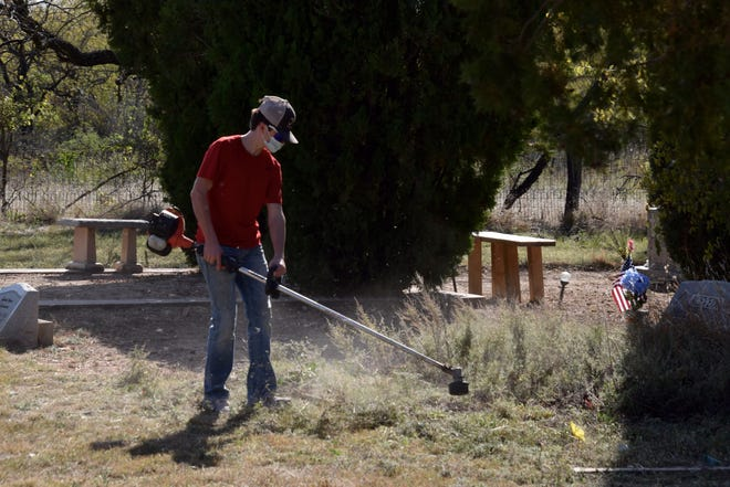 A Miles High School student cuts away weeds from a grave at the cemetery in Miles.