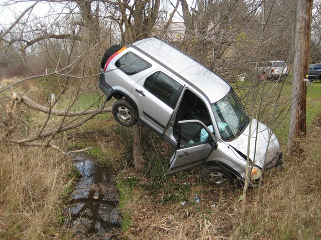 This Honda CRV struck a telephone pole, breaking it, and ended up suspended in trees after an allegedly impaired Cuyahoga Falls man drove it off the side of Route 303 in Streetsboro on Friday morning.