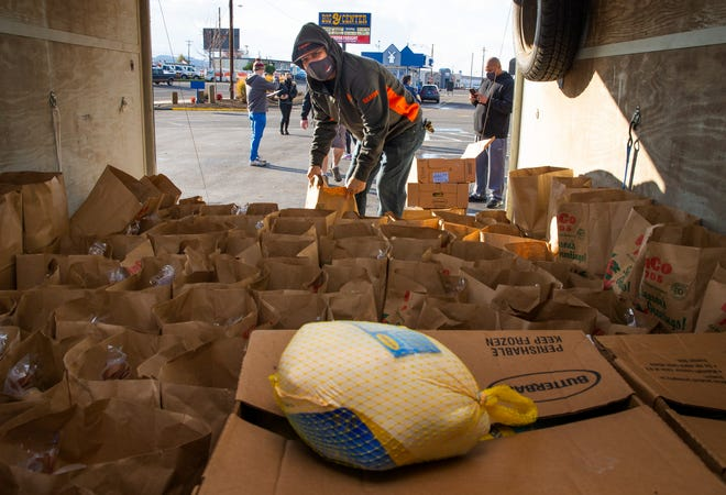 Volunteer Keiki Rauschenburg helps distribute Thanksgiving meals donated by Keith and Amy Lewis, who own the Once Famous Grill and Quacker's Last Stop Sports Bar in Eugene.