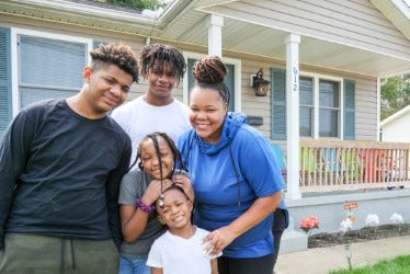 The Wesley family poses in front of their new southeast Canton home built by Habitat for Humanity East Central Ohio.