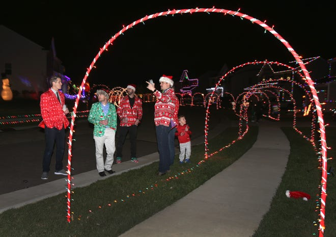 Neighbors, from left, Tyler Schwendiman, Daniel Butts, Brett Clevidence, John Boyd, Andrew Bounds (hidden) and Matthew Bounds are decked out in their Christmas-themed garb as they enjoy the lights along their street in Jackson Township. The neighbors will hold a Christmas Walk Dec. 5.