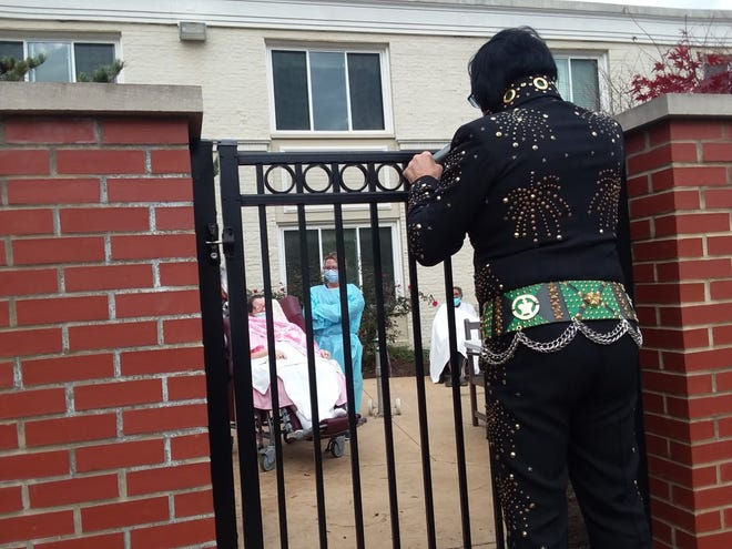 Elvis Presley impersonator Gary Shreve of Canton sings Friday for a hospice patient at The Laurels of Canton. Shreve's performance was a surprise for ardent Elvis fan Patricia Franklin (left). Because of COVID-19 restrictions, Shreve had to perform behind a fence.
