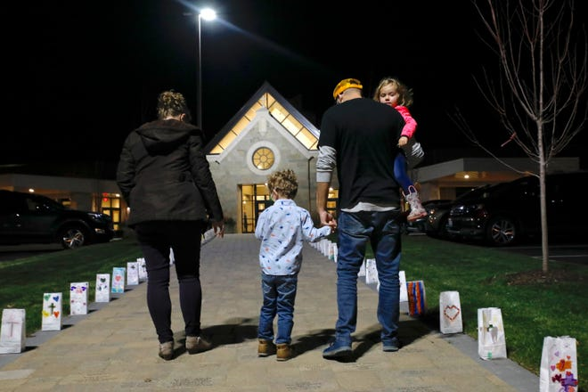 The Stevens family of Rockford walk past decorated luminaries Thursday, Nov. 19, 2020, while attending a grand reopening dedication Mass celebrating the upgrades and renovations at Holy Family Church in Rockford.