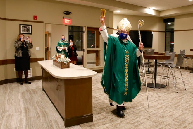 Bishop David J. Malloy blesses the Frassati Room at Holy Family Church Thursday, Nov. 19, 2020, during a grand reopening dedication Mass celebrating the upgrades and renovations at the church.