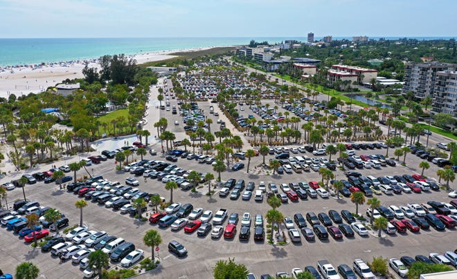 A full Siesta Key Beach parking lot in May with a view of some of the larger condominiums and hotels on the barrier island.