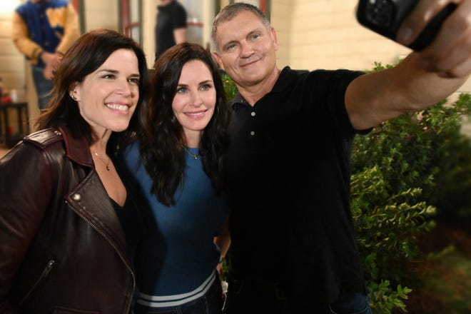 """Neve Campbell (left to right), Courteney Cox and Kevin Williamson take a celebratory selfie on the Wilmington set of """"Scream."""""""