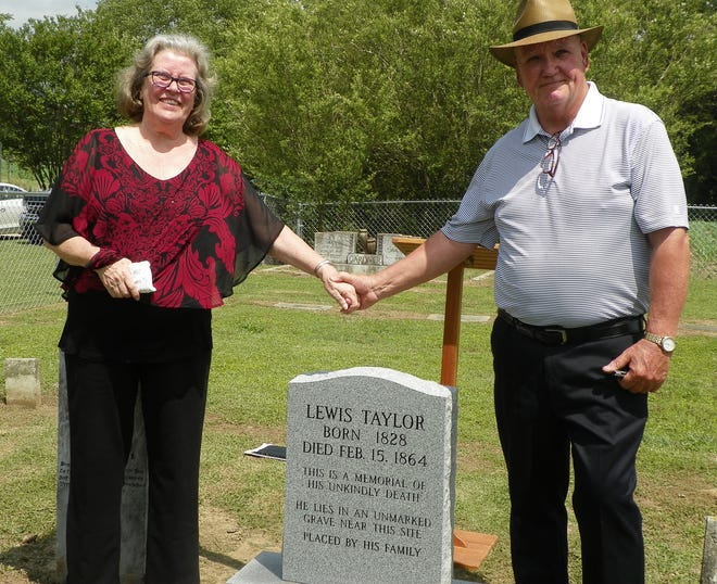 Marshall Taylor stands with his wife at the gravestone of his great-great-grandfather Lewis Taylor. Lewis' grave had been left unmarked and forgotten since he was hanged in Kinston in 1864. [Contributed photo]