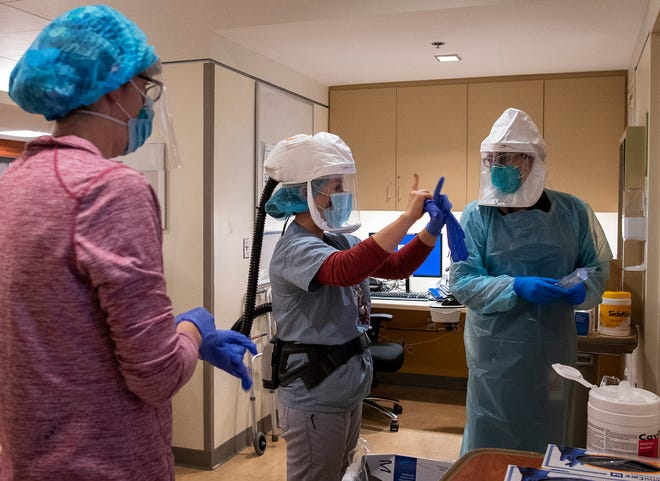 Health care workers put on personal protective equipment, including powered air purifying respirators, before entering the room of a patient with COVID-19 Nov. 18 at UMass Memorial Medical Center - University Campus.