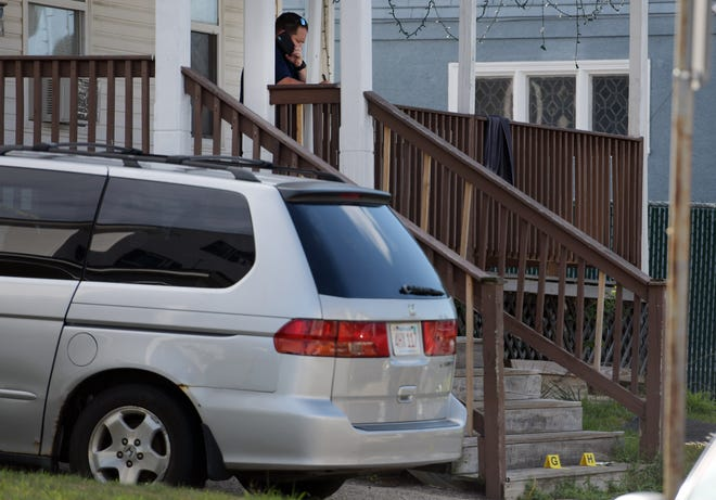 A police officer talks on his phone at 38 King St. in Worcester, while investigating a fatal shooting there on Aug. 3, 2020.