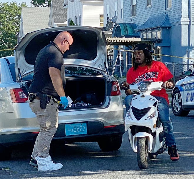 Jacob Grice, right, talks to Worcester police investigator on Monday, Aug. 3, 2020. at the scene of a slaying at 38 King St., Worcester.Grice faces charges in the case.