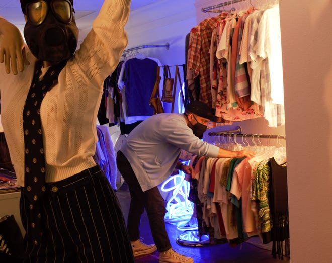 Jose Peruyero, one of five owners of The How Bazar in the Seagle Building, arranges clothes on a rack in the store. The store sells thrifted pieces that have been brought back to life through customizations by local Gainesville artists and tailors.