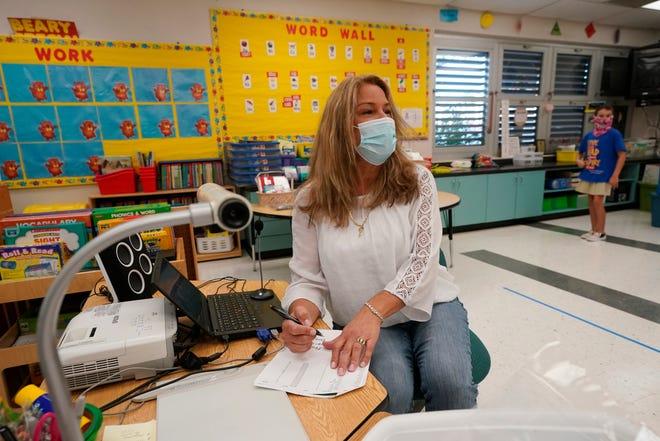 A kindergarten teacher takes attendance.