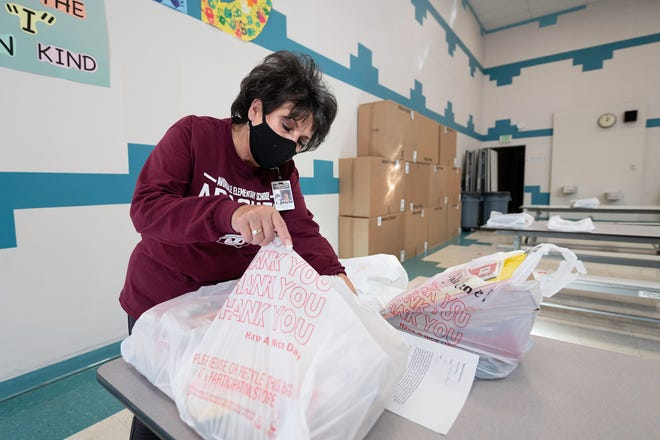 Avondale Elementary School principal Carmen Avalos fills bags of school supplies that was distributed to students for at home learning on Thursday November 19, 2020.