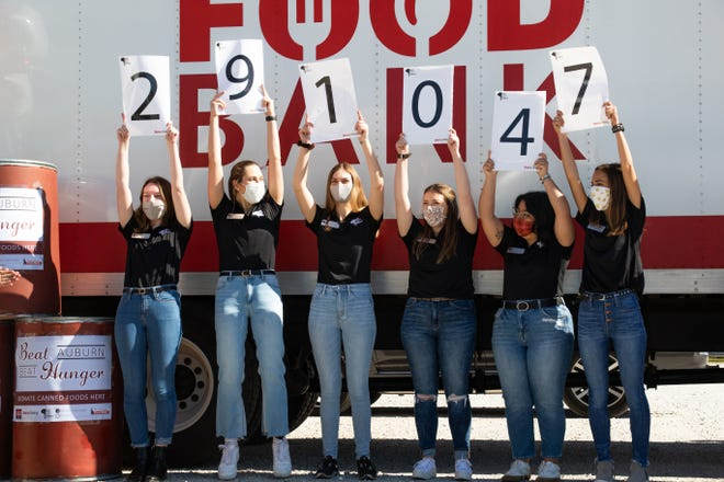 University of Alabama students display the total amount of food gathered in the Beat Auburn Beat Hunger food drive Friday, Nov. 20, 2020, at the West Alabama Food Bank. [Photo/Hannah Saad]