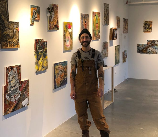 Brookline artist David Meyers posing with some of his works.