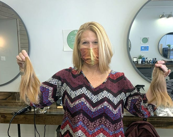 """Stow resident Beth Tramontozzi Sullivan displays 10 inches of her strawberry blond hair that she donated to Wigs for Kids, in memory of her father, """"Nino"""" Tramontozzi, a 90-year-old retired Boston firefighter, who was a victim of COVID-19."""