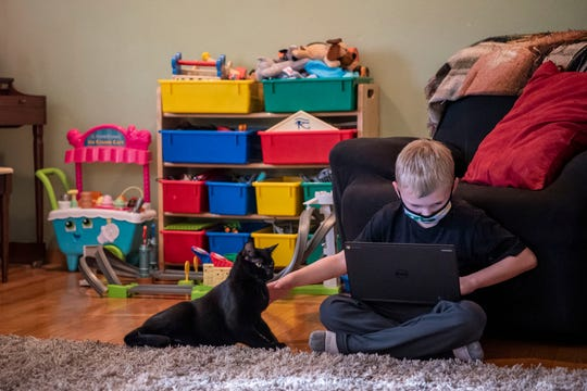 Dylan Canfield, 8, plays with his cat Chauncey while completing schoolwork on Friday, Nov. 20, 2020 at his home in Battle Creek, Mich.