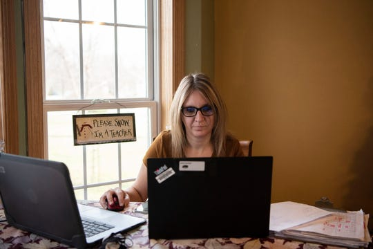 Pennfield fourth grade teacher Karin Canfield grades math tests on Friday, Nov. 20, 2020 at her home in Battle Creek, Mich.