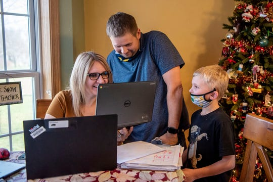 Karin and Kevin Canfield, who are both elementary school teachers working from home, attempt to find the link to their son Dylan's online gym class on Friday, Nov. 20, 2020 at their home in Battle Creek, Mich.