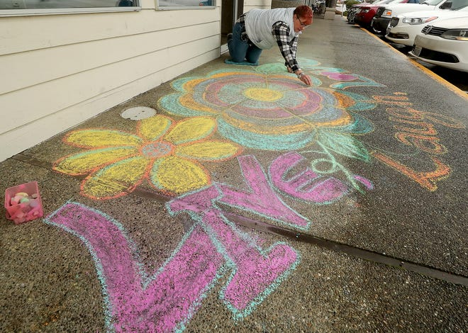 Chalk artist Michele Fletcher puts the finishing touches on her work on the sidewalk at the Mariner Square plaza in Silverdale on Nov. 20.