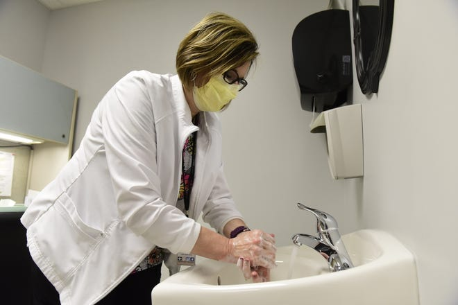 Erin Barnett, RN, a public health nurse for Crawford County Public Health, washes her hands thoroughly for at least 20 seconds several times throughout the day to safeguard against COVID.