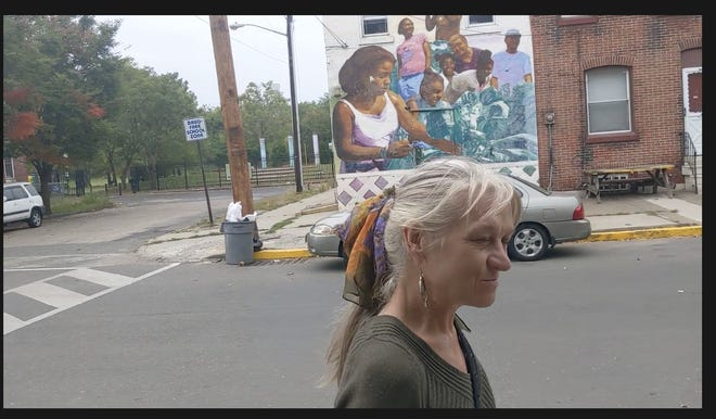 A screenshot from a YouTube video shows poet and South Camden resident Cassie MacDonald as she walks through the neighborhood and past a mural at Jasper and S. 4th streets.