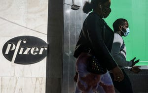Dalam file foto 9 November 2020 ini, pejalan kaki berjalan melewati kantor pusat dunia Pfizer di New York.