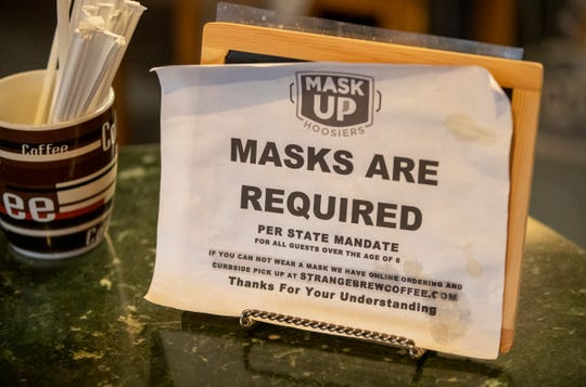 Signage that explains the policy at Strange Brew Coffee, Greenwood, Wednesday, Nov. 11, 2020. The shop has had to navigate an increase in upset customers, as they don't want to wear masks, and resist the store's curbside option.