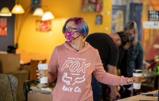 Rachel Van Winkle, Indianapolis, gets orders for customers at Strange Brew Coffee, Greenwood, Wednesday, Nov. 11, 2020. The shop has had to navigate an increase in upset customers, as they don't want to wear masks, and resist the store's curbside option.