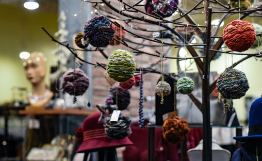 Crafted with hand-spun yarns, local artist Deb Cholewicki's 'Holiday orbs' are displayed at Grace Boutique in Old Town Thursday, Nov. 20, 2020, in Lansing.