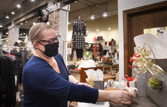 Summer Schriner, owner of Grace Boutique in Old Town wraps holiday gifts Thursday evening, Nov. 19, 2020, in Lansing. Customers may place orders online or by phone.