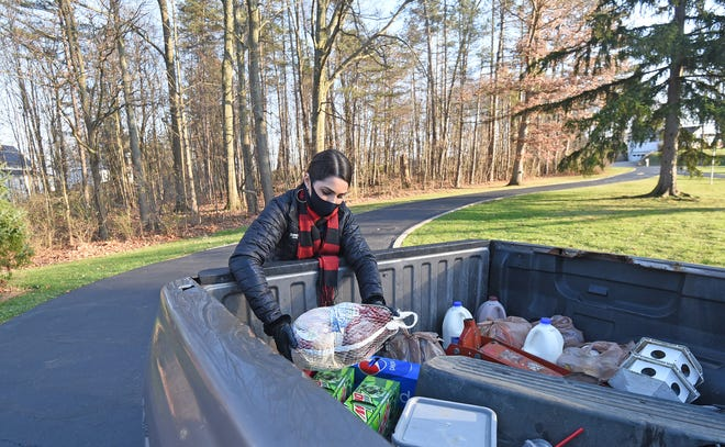 Rachel Rinehardt delivers a turkey to the bed of a pickup truck Friday afternoon.