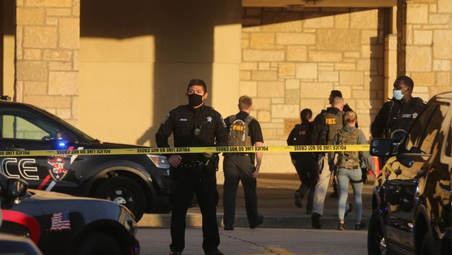 Law enforcement officials arrive at the Mayfair Mall following a shooting on Friday, Nov. 20, 2020.