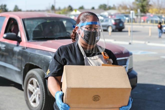Annie Marmolejo puts food boxes in cars during a Thanksgiving meal food distribution at Gadsden Middle School in Anthony on Friday, Nov. 20, 2020.
