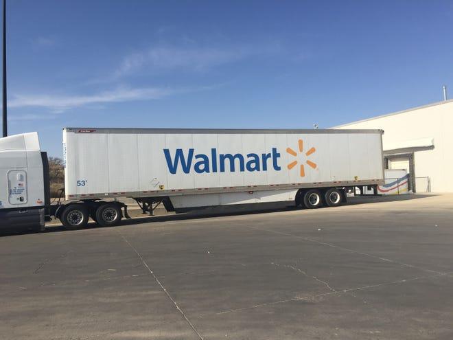 A semi with supplies pulls into a Walmart Supercenter.