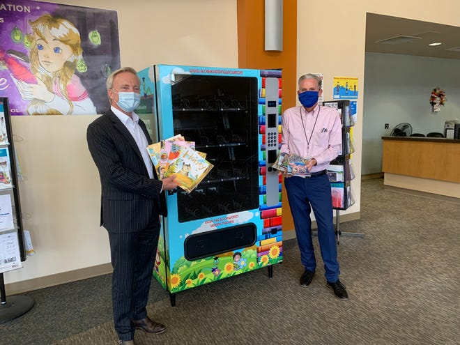 Superintendent Scott Bailey, left, and Michael Wihite show off Inchy the Bookworm Vending Machine.