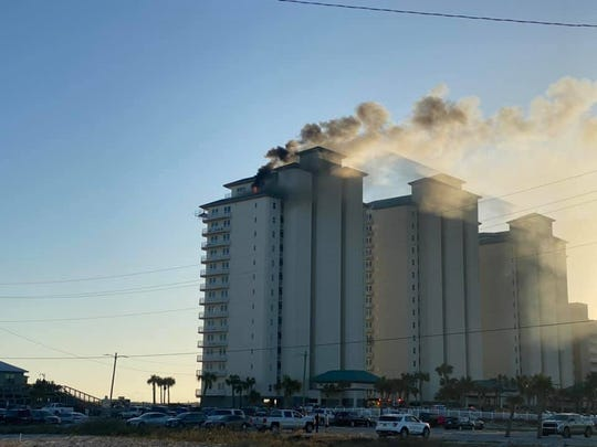 Black smoke rises from a roof fire at Summerwind Resort on Navarre Beach on Thursday. The fire was extinguished and no one was injured.