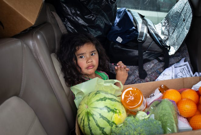 Amelia Calles, 3, sits next to a food box on March 25, 2020, at the St. Mary's Food Bank Alliance in west Phoenix.
