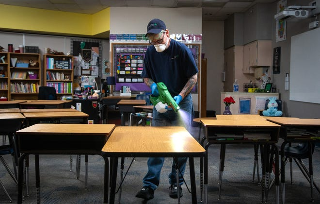 Robert Truman, with SSC Services for Education, uses an electrostatic sprayer to sanitize a classroom, March 12, 2020, at Kyrene de la Mirada Elementary School in Chandler, Arizona.