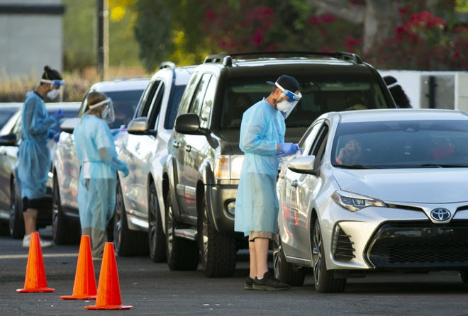 People line up in their vehicles to get tested for COVID-19 at a drive-thru rapid testing site in Scottsdale on Nov. 19, 2020.