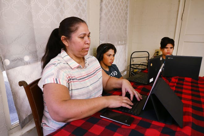 Imelda Hartley sits with her sons Jean Paul Ortiz and Jesus Ortiz (right) as they do their schoolwork online from the kitchen table in Phoenix on Nov 19, 2020.