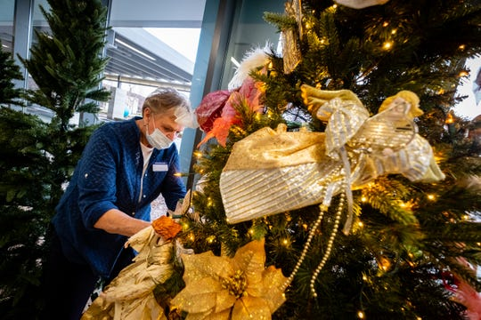 Antoinette Tucker works to decorate a tree ahead of this year's Festival of Trees Friday, Nov. 20, 2020, at Mclaren Port Huron. This year's event is being held in the hospital's lobby so people can drive or walk by outside the hospital to see the trees.
