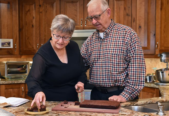 Heather Tyreman, with her husband Bill Finney, slices the brownies she baked for a Thanksgiving food swap with several other Reno families instead of gathering in person this year.