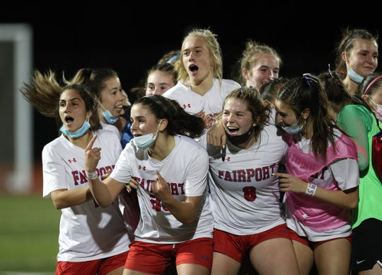 Fairport players celebrate their 1-0 win over Hilton winning the Class AA title.