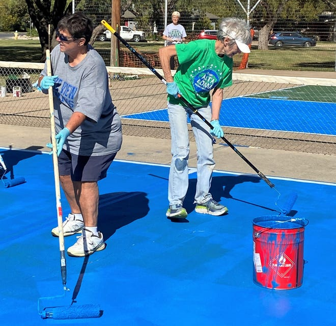 Margie Lyons, left, and Pam Holubec work on painting  public pickleball courts at San Angelo's Brown Park at the corner of Johnson Street and West Twohig. Debby Scofield is in the background. Nets will be added in the future.
