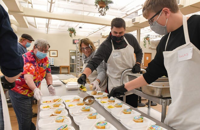 Volunteers package to-go meals on Wednesday, November 18, at The Banquet in Sioux Falls.